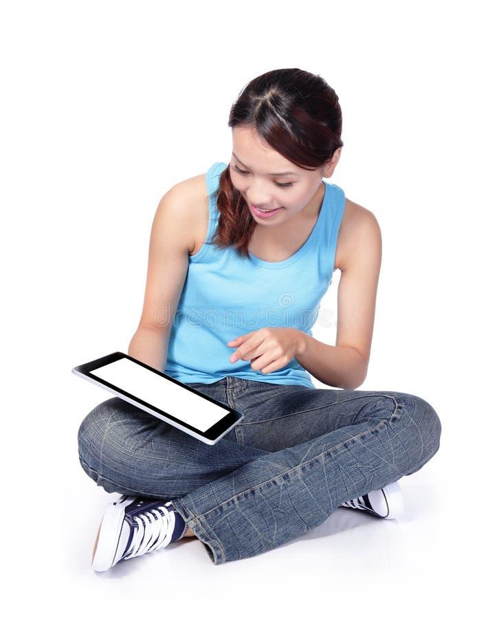 L'étudiante s'asseyent et à l'aide du comprimé numérique image libre de droits