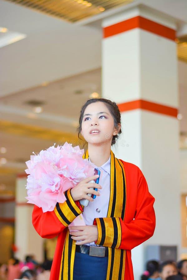 L'étudiante thaïlandaise dans la robe scolaire attend avec intérêt l'avenir dans son jour  photo libre de droits