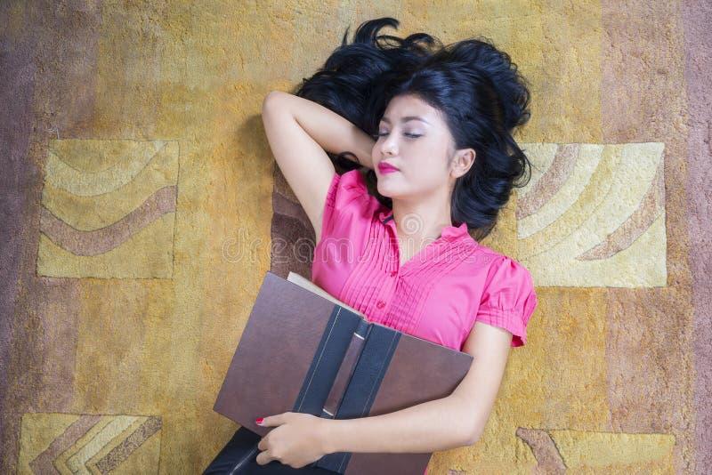 L'étudiante tient le livre et le sommeil sur le tapis photographie stock libre de droits