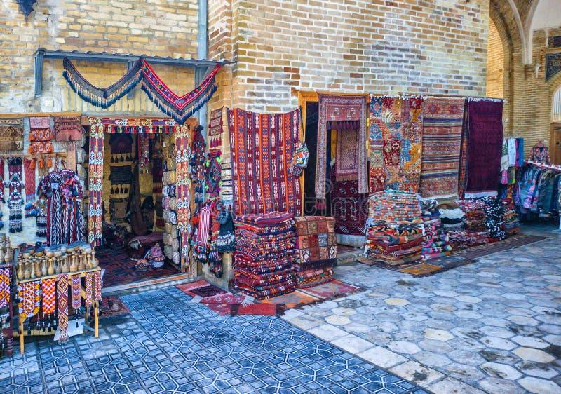 L'éventail des tapis fabriqués à la main dans le style traditionnel dans la petite stalle au bazar de Toqi Sarrafon, Boukhara photo libre de droits