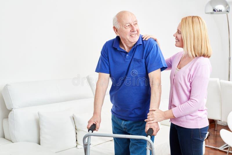 L'aîné avec le marcheur fait la réadaptation avec le thérapeute image libre de droits