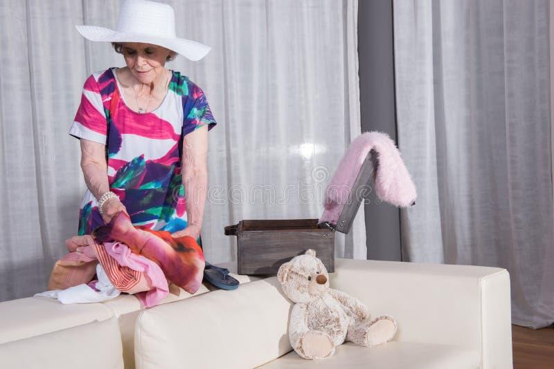 L'aîné féminin actif emballe la valise de vintage pour des vacances d'été photos stock