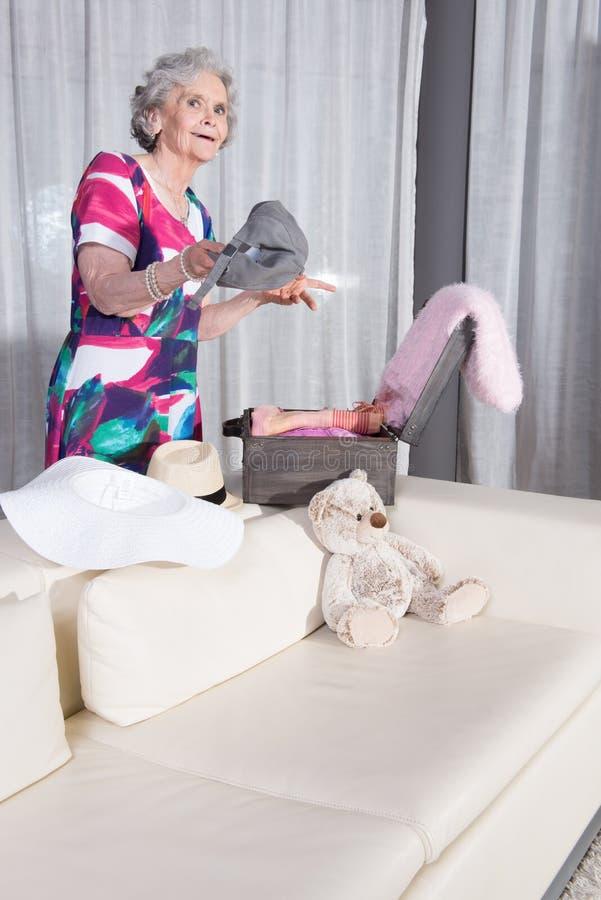 L'aîné féminin actif emballe la valise de vintage pour des vacances d'été photos libres de droits