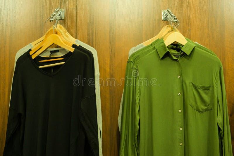 L'abbigliamento degli uomini sui ganci in un deposito di modo Camicia verde e pullover nero Priorità bassa di legno Concetto di a immagini stock libere da diritti