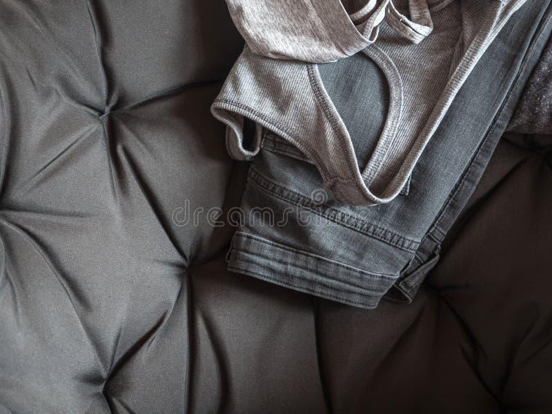 L'abbigliamento delle donne grige su una sedia grigia Camicia, jeans Fondo neutrale fotografie stock