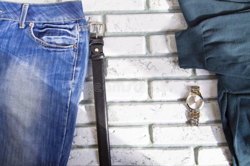 L'abbigliamento e gli accessori degli uomini casuali moderni sul fondo bianco del mattone, luce solare fotografia stock