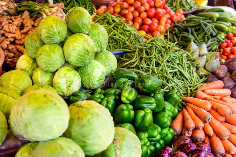 L'abbondanza di verdure nei mercati di strada asiatici Cariche di verdure diverse a bazaar, in India, si chiudono Cavoli, carote, fotografia stock