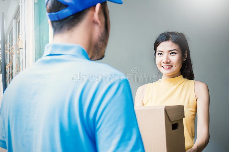 L'accettazione asiatica della donna riceve una consegna delle scatole dall'uomo dell'asiatico della consegna fotografia stock libera da diritti