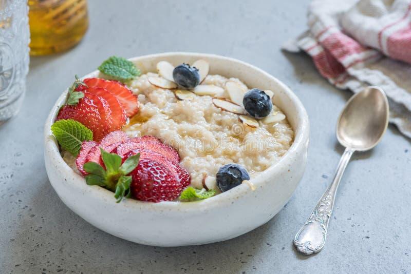 L'acciaio ha tagliato il porridge della farina d'avena con la fragola ed il mirtillo per la prima colazione fotografie stock libere da diritti