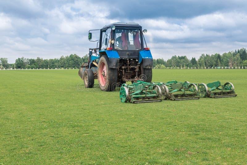 L'acconciatura meccanizzata di un prato inglese verde Falciatrice nel campo L'erba falciata vola da sotto un sego fotografie stock