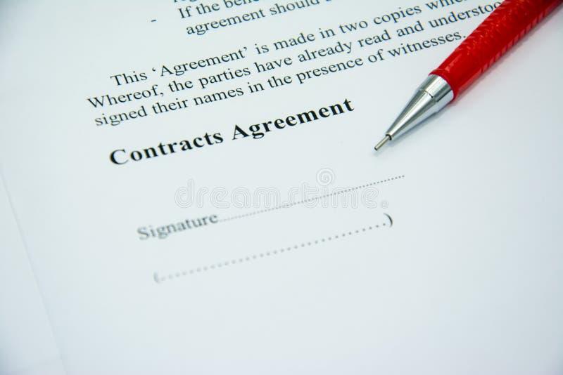 L'accord de contrats se connectent le papier de document avec le stylo rouge photos stock