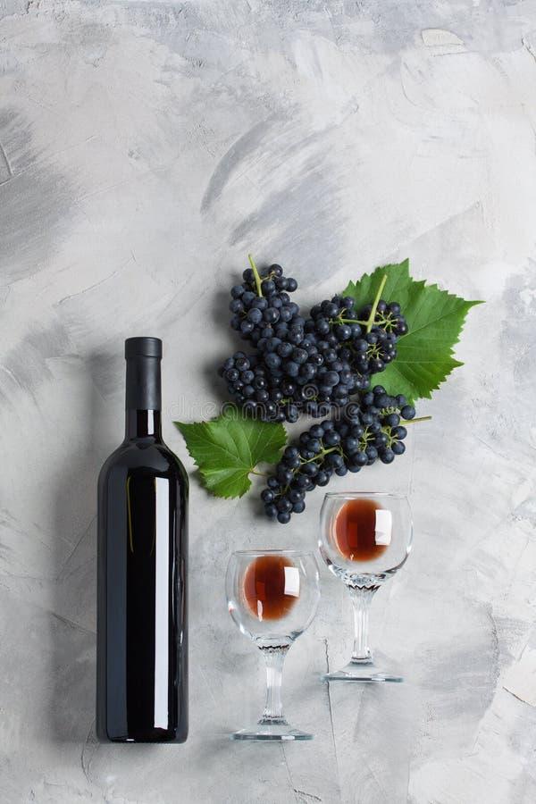 L'acino d'uva dei vetri da bottiglia lascia lo spazio concreto della copia del fondo fotografie stock libere da diritti
