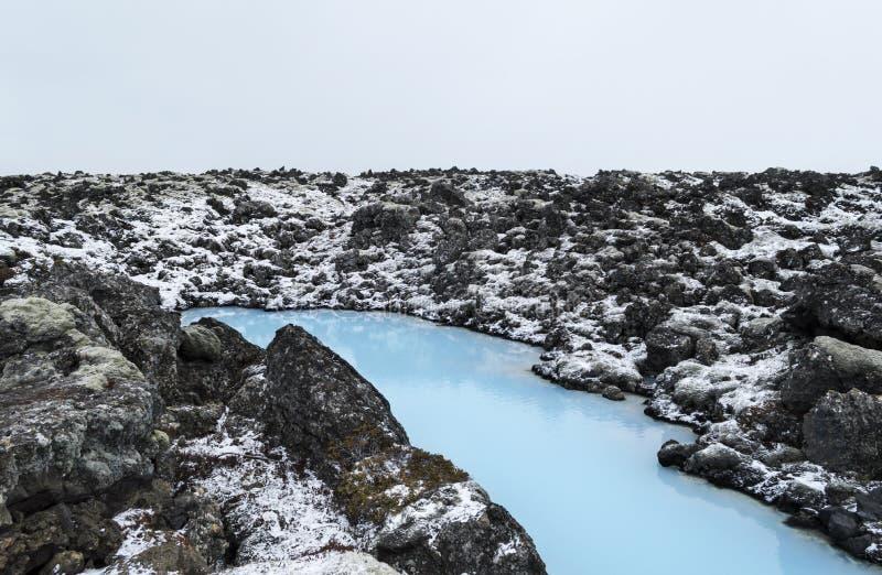 L'acqua blu fra le pietre della lava coperte di muschio fotografia stock libera da diritti