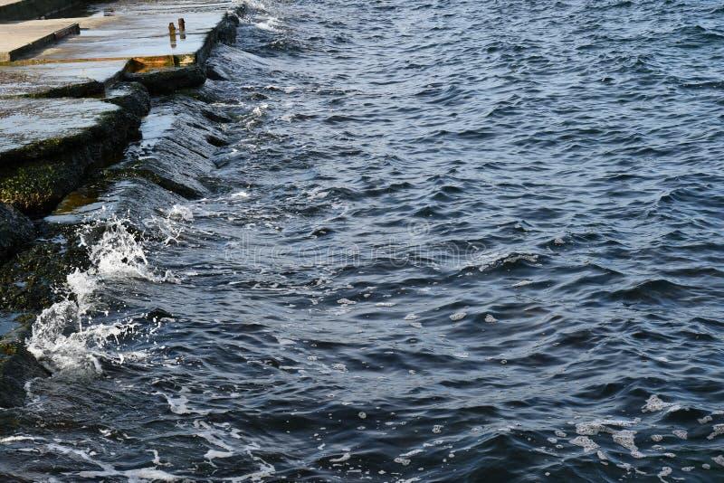L'acqua con struttura ondulata e piccolo blu scuro spruzza fotografie stock libere da diritti