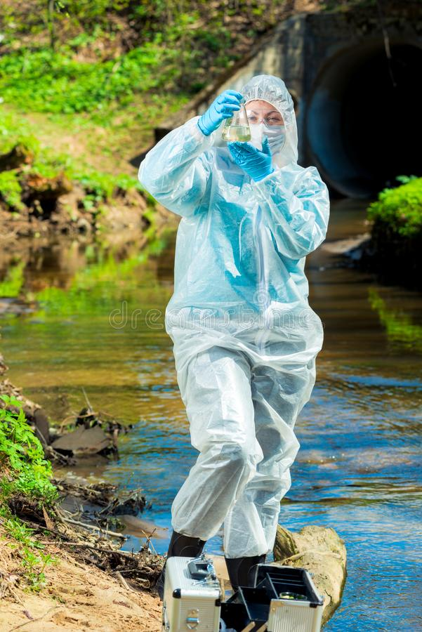 l'acqua di fogna pericolosa, uno scienziato preleva un campione dell'acqua in protettivo immagini stock