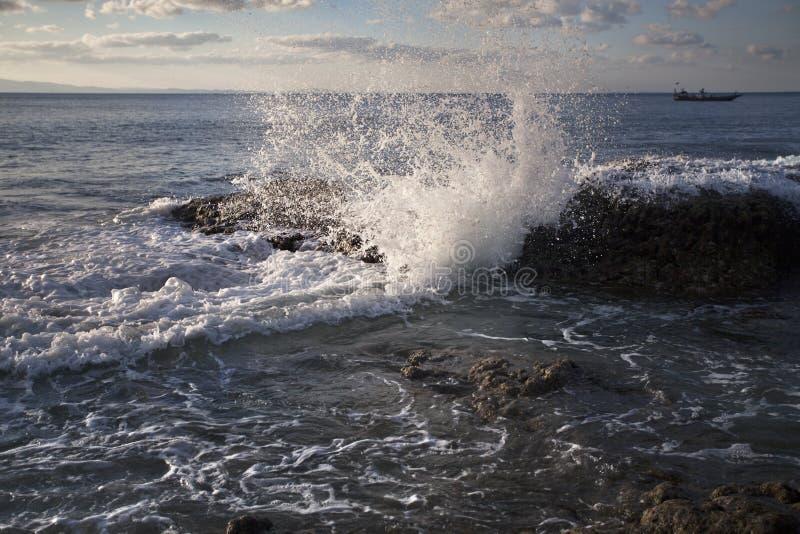 L'acqua di mare colpisce una roccia alla riva di mare immagini stock