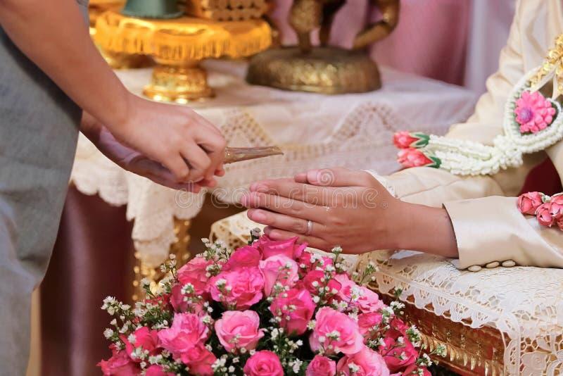 L'acqua di versamento dell'ospite con le mani dello sposo e della sposa in acqua rilancia la cerimonia Nozze tradizionali tailand fotografia stock