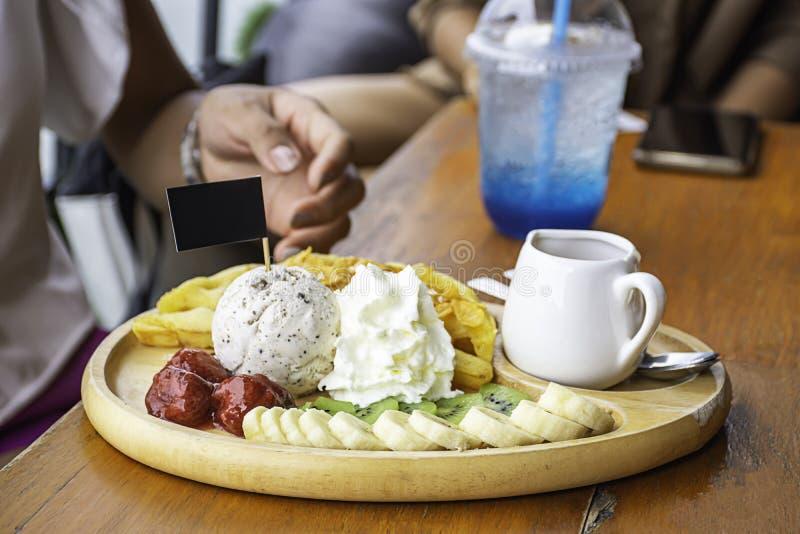 L'acqua dolce versa sulla cialda con il gelato e sui frutti compreso le banane, il kiwi e le fragole in piatto di legno sulla tav fotografia stock