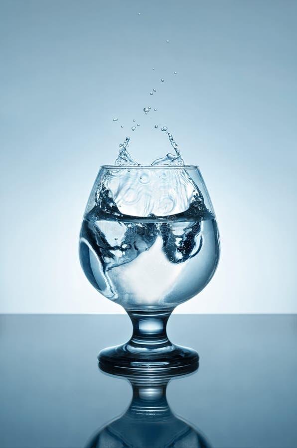L'acqua minerale con ghiaccio e spruzza immagine stock
