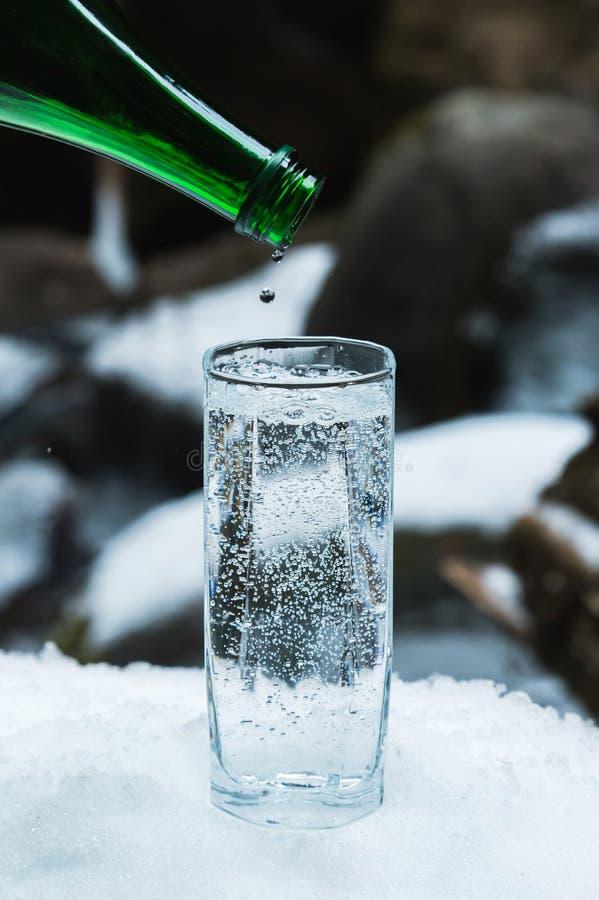 L'acqua minerale pura è versata da una bottiglia verde di vetro in un becher del vetro trasparente fino all'ultima goccia fotografie stock libere da diritti