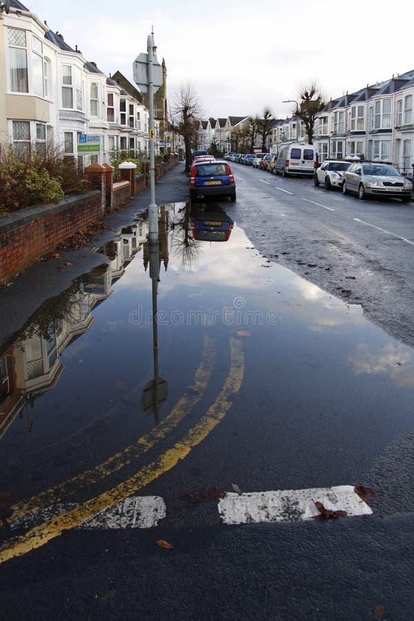 L'acqua piovana è straripata in una strada cittadina immagini stock libere da diritti