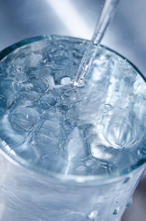 L'acqua potabile sicura pulita di versamento dal rubinetto convoglia a casa fotografia stock libera da diritti