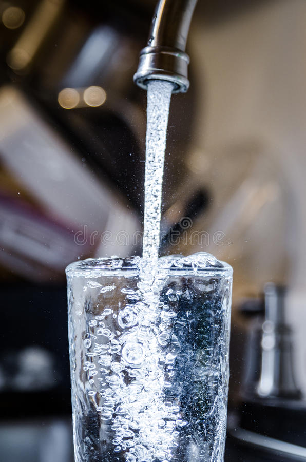 L'acqua potabile sicura pulita di versamento dal rubinetto convoglia a casa immagini stock
