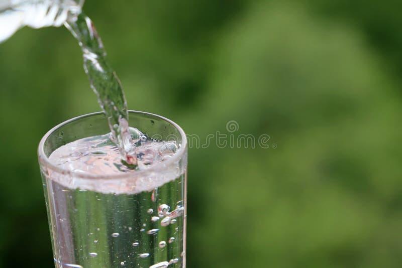 L'acqua pulita versa da una bottiglia in bicchiere sul fondo verde della natura immagine stock libera da diritti