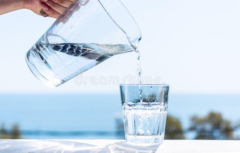 L'acqua purificata è versata da una brocca di vetro in un vetro fotografie stock libere da diritti
