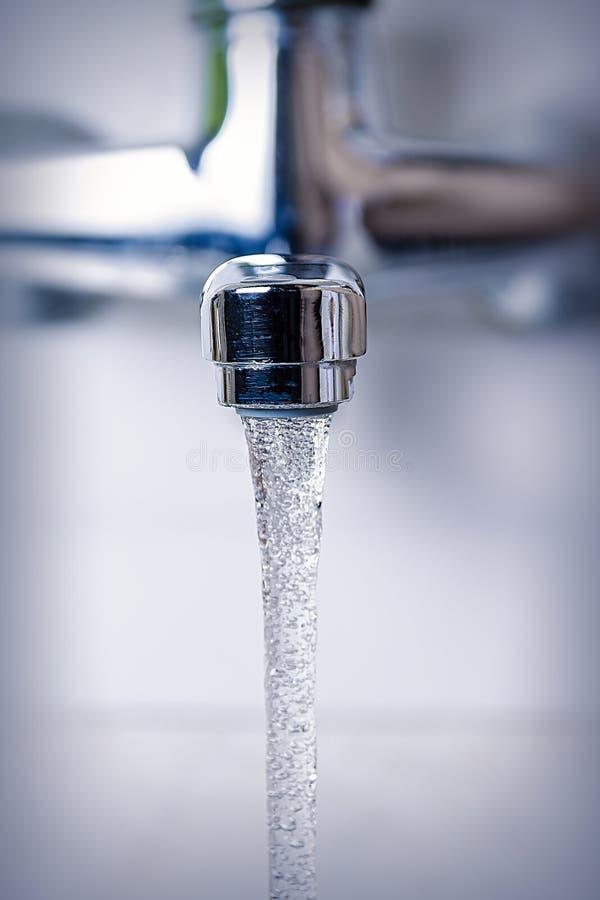 l'acqua scorre dal rubinetto della cucina, da vicino fotografia stock libera da diritti
