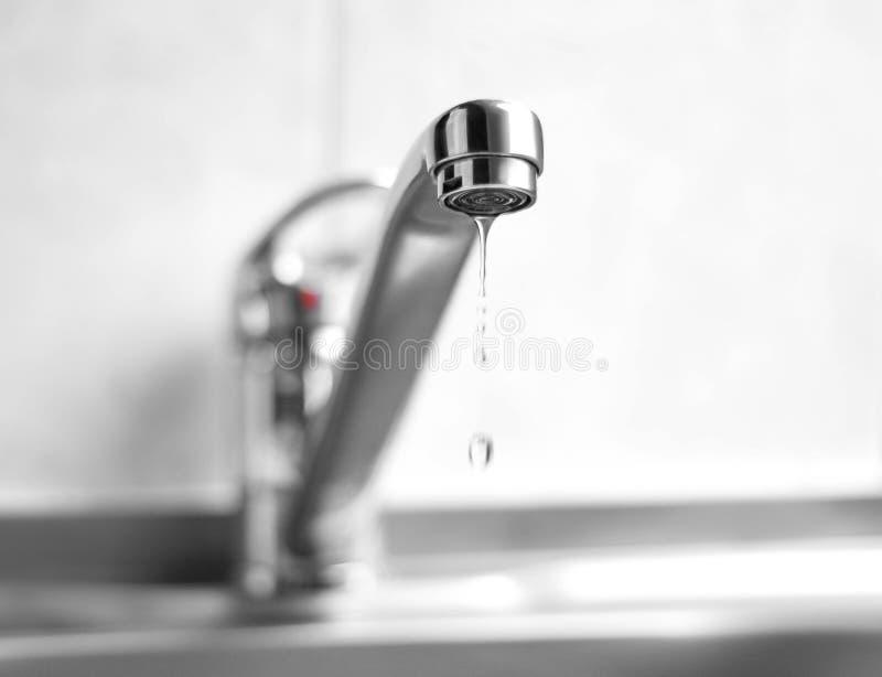 L'acqua sta gocciolando da un rubinetto di acqua del metallo Fine in su fotografia stock libera da diritti