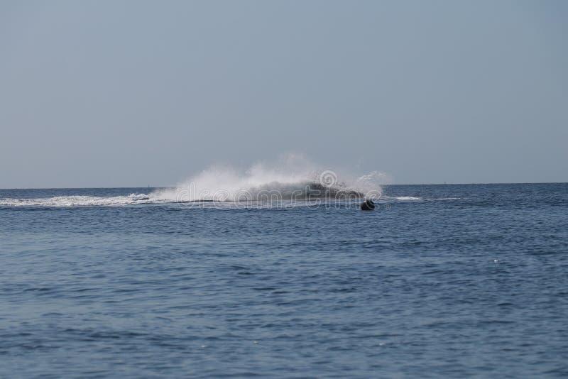 L'acquascooter all'alta velocità in acqua spruzza Rotolando su un acquascooter di estate lungo il mare fotografia stock libera da diritti