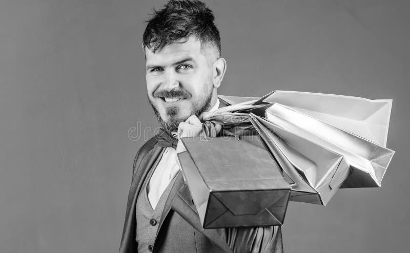 L'acquisto con lo sconto gode dell'acquisto L'uomo d'affari elegante barbuto dell'uomo porta i sacchetti della spesa su fondo gri fotografia stock libera da diritti