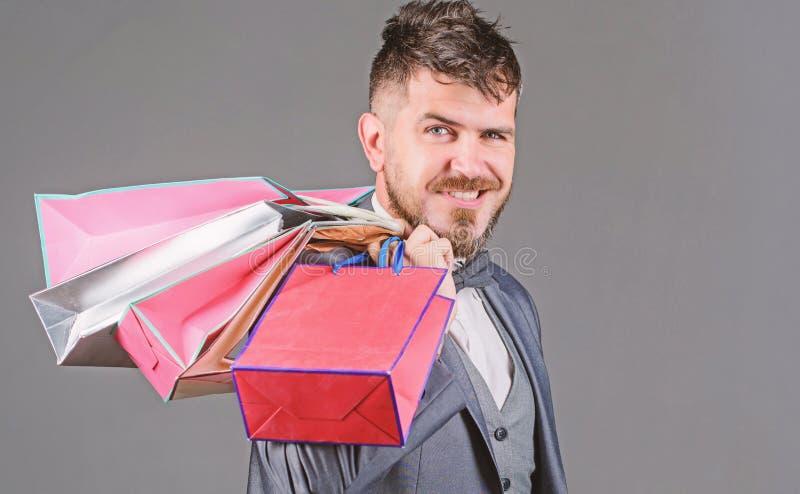 L'acquisto con lo sconto gode dell'acquisto L'uomo d'affari elegante barbuto dell'uomo porta i sacchetti della spesa su fondo gri fotografie stock libere da diritti