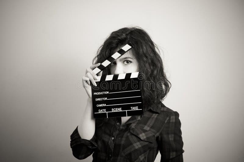 L'actrice de femme observe le portrait derrière le panneau de clapet de film photos stock
