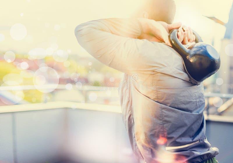 L'addestramento del giovane con i pesi, facenti gli edifici occupati, sulla città di trascuratezza del terrazzo soleggiato, ha of immagini stock