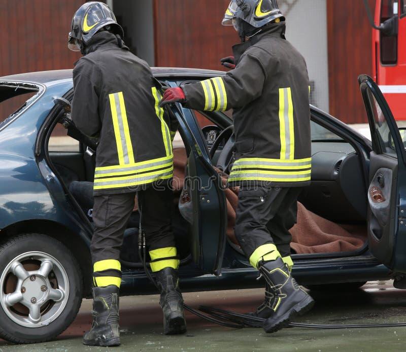 L'addestramento del pompiere da estrarre ha intrappolato l'uomo nell'automobile immagini stock