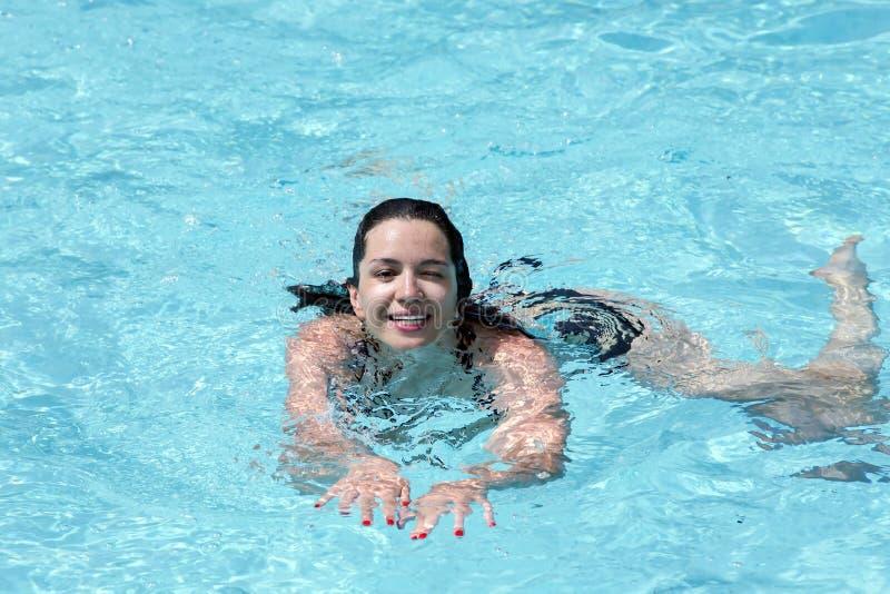 L'addestramento sorridente della ragazza in un turchese innaffia la piscina all'aperto fotografie stock