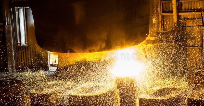 L'addetto alla lavorazione dell'acciaio cola il metallo liquido negli stampi dal carro armato fotografie stock libere da diritti