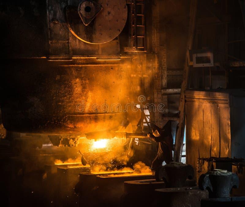 L'addetto alla lavorazione dell'acciaio cola il metallo liquido negli stampi dal carro armato fotografia stock libera da diritti