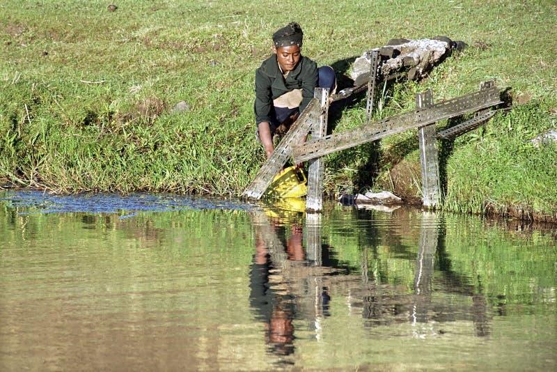 L'ado éthiopien obtient l'eau potable de la source d'eau images libres de droits