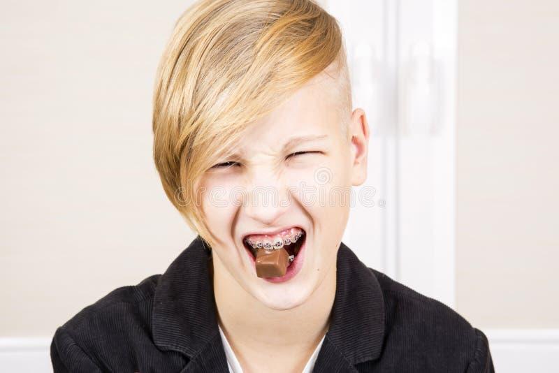L'ado avec des accolades sur ses dents mange du chocolat photo stock