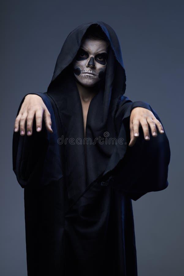 L'ado avec le cap de crâne de maquillage a étiré des bras en avant photos stock