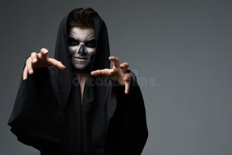 L'ado avec le cap de crâne de maquillage veut le grippage images stock