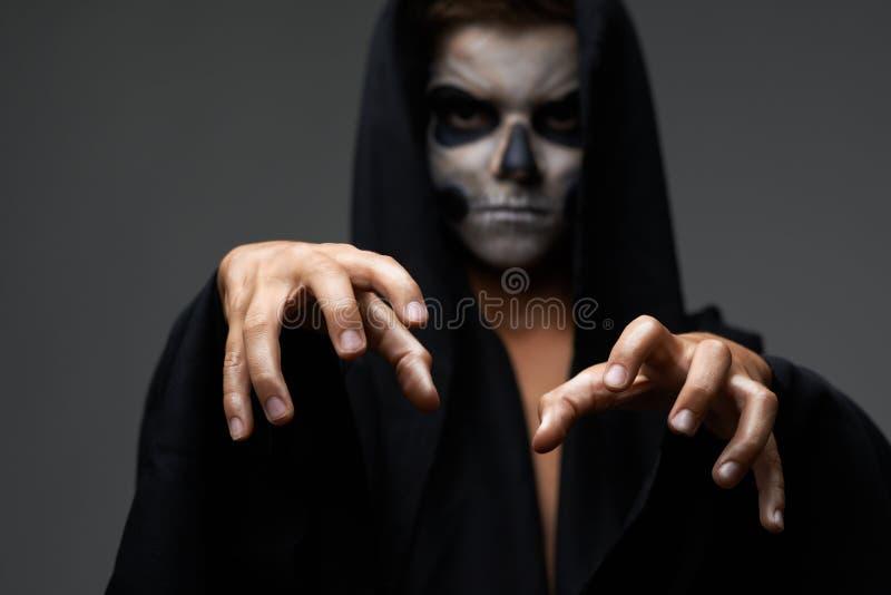 L'ado avec le cap de crâne de maquillage veut le grippage image stock