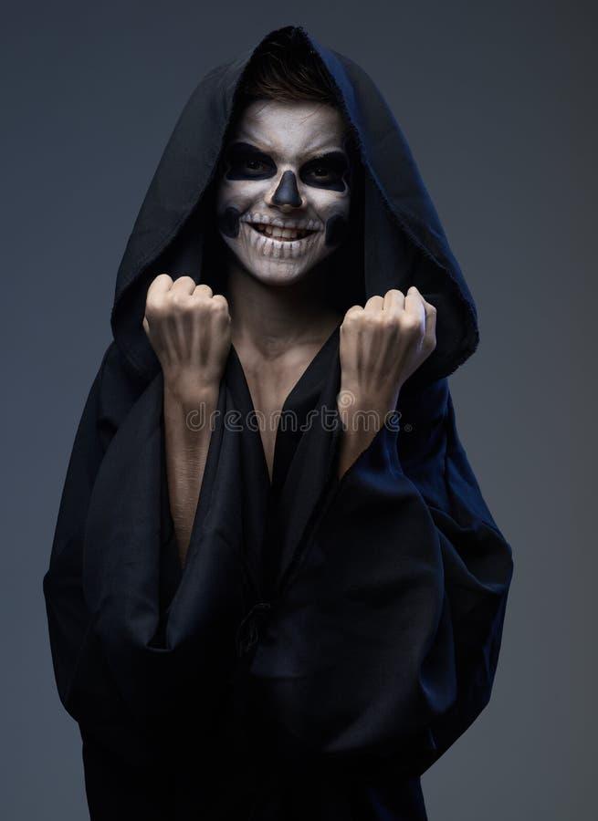 L'ado avec le crâne de maquillage montre des poings photo libre de droits