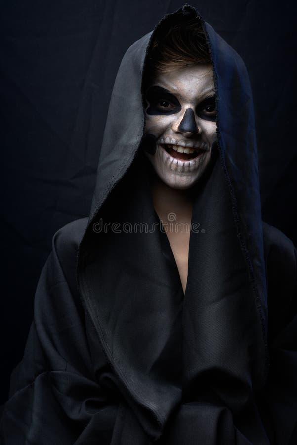 L'ado avec le maquillage du crâne dans le manteau noir rit photo libre de droits