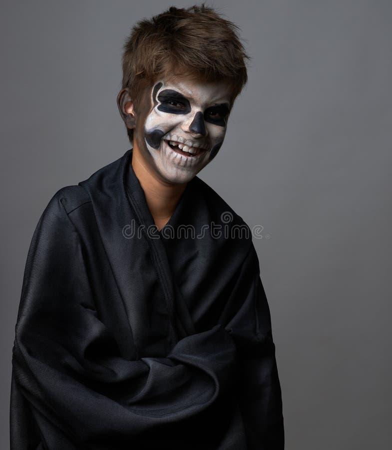 L'ado avec le maquillage du crâne dans le manteau noir rit photos stock