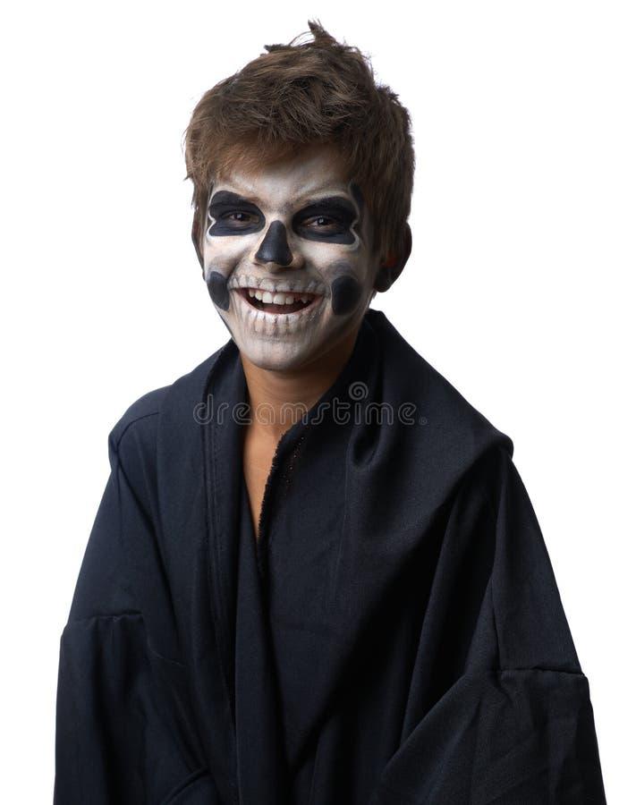 L'ado avec le maquillage du crâne dans le manteau noir rit image stock