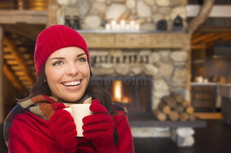L'ado confortable de métis apprécie le cacao chaud par une cheminée chaude photo stock